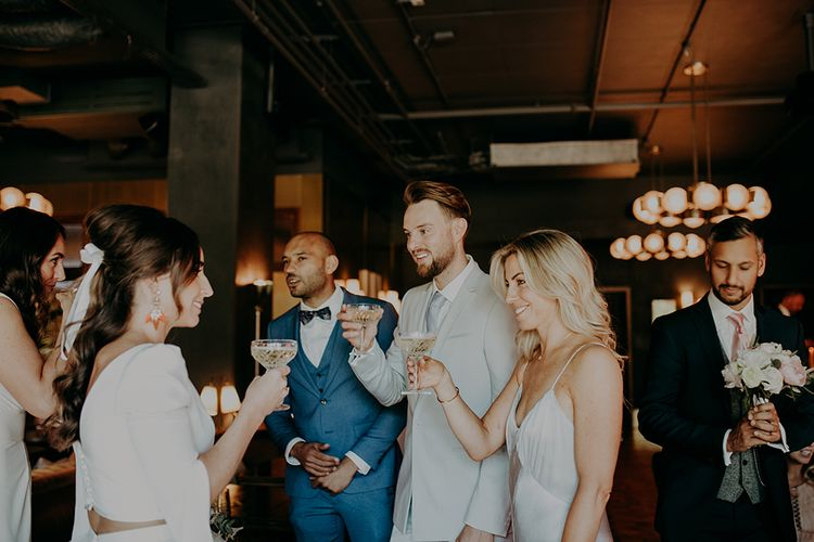 Bride and Wedding Guests Enjoying Champagne in Coupe Glasses