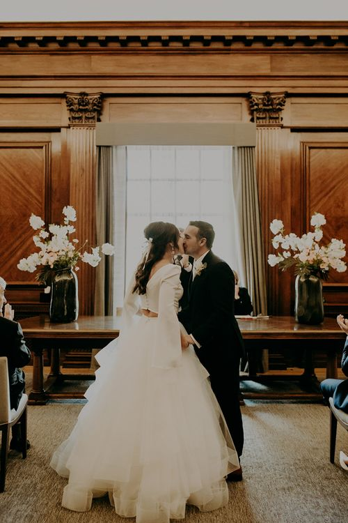 Bride in Sassi Holford; Tamara Top & Tulle Fearn Skirt and Groom in Cad in The Dandy Suit Kissing at Wedding Ceremony