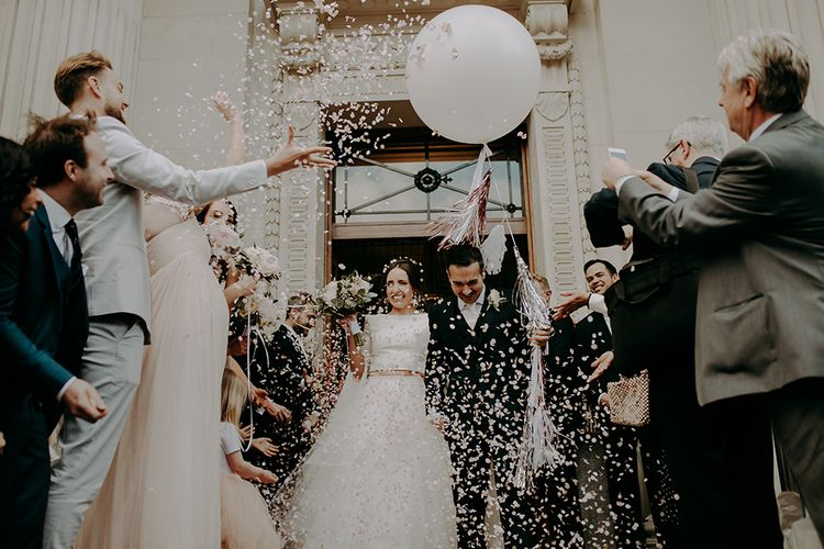 Confetti Exit with Bride in Sassi Holford; Tamara Top & Tulle Fearn Skirt and Groom in Cad in The Dandy Suit
