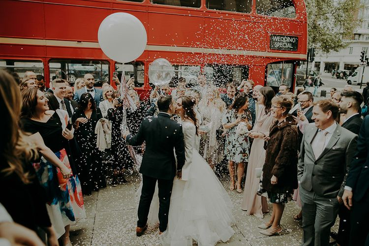 Confetti Moment with Bride in Sassi Holford; Tamara Top & Tulle Fearn Skirt and Groom in Cad in The Dandy Suit