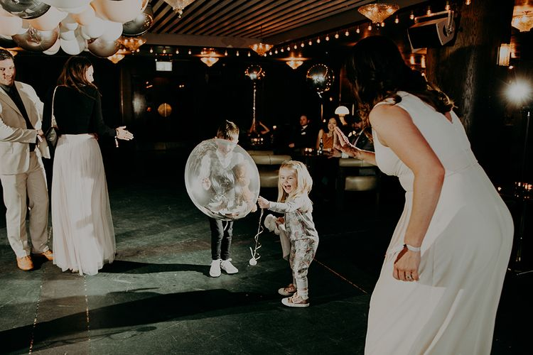 Mini Wedding Guests Playing with Clear Balloon