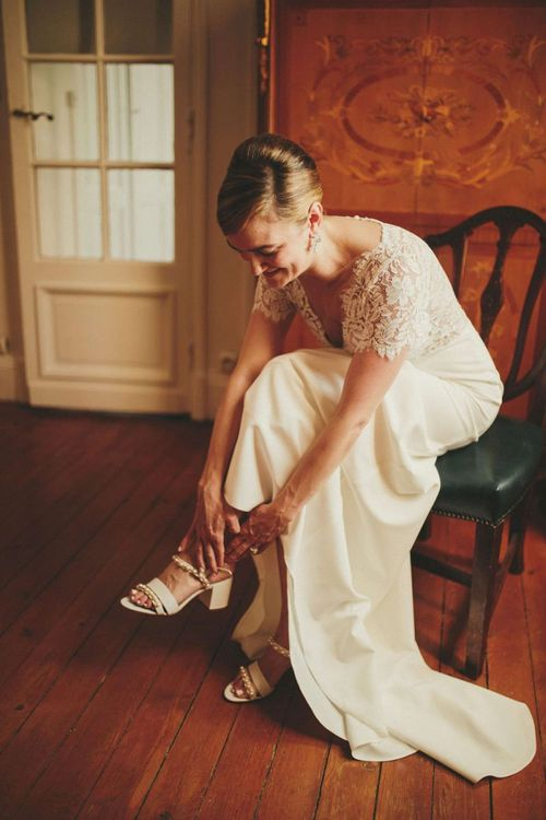 Bride in Sarah Seven dress putting on her wedding shoes
