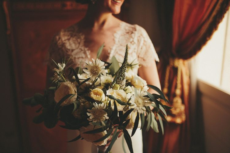 Bride in lace detail Sarah Seven wedding dress with white bouquet