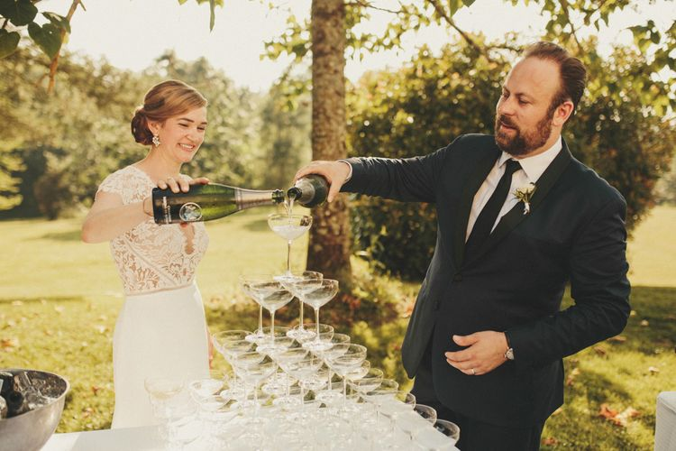 Bride in Sarah Seven dress with new husband with Champagne tower