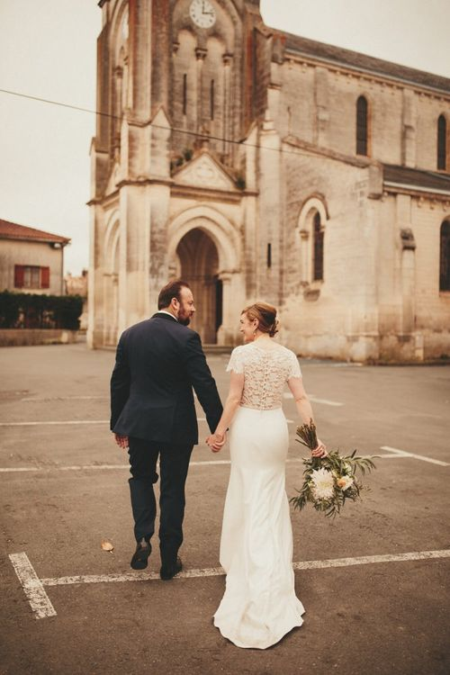 Lace detail Sarah Seven wedding dress with groom at French wedding venue