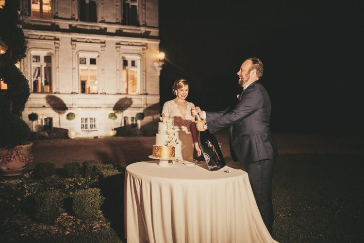 Bride and groom cut the white and gold wedding cake