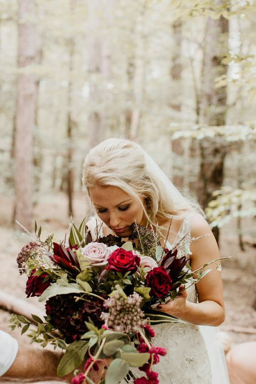 Deep Red Rose, Greenery & King Protea Bouquet Bride in Maggie Sottero Gown | Burgundy Outdoor Woodland Ceremony & Country Tipi & Horse Bar Reception at The Ancient Woodland, Hertfordshire, Planned & Styled by Caroline Hitchcock Events | Alex Wysocki Photography | DgtlCouture Film