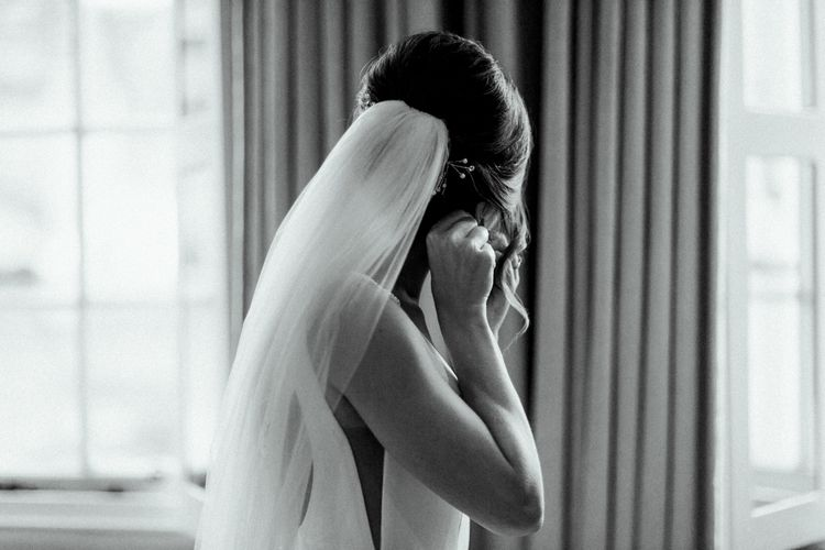 Wedding Morning with Bride Putting on Earrings Wearing a Cathedral Veil