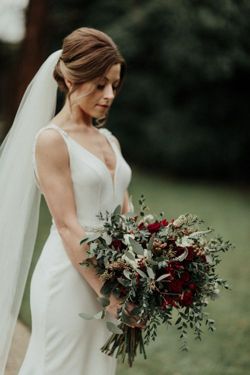 Bride in Essense of Australia Wedding Dress with Straps Holding a Red Flower and Foliage Winter Wedding Bouquet