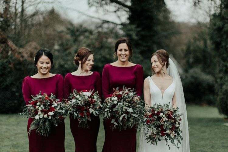 Bridal Party with Bridesmaids in Burgundy Dresses and Bride in Essense of Australia Wedding Dress Holding Red and Foliage Winter Bouquets