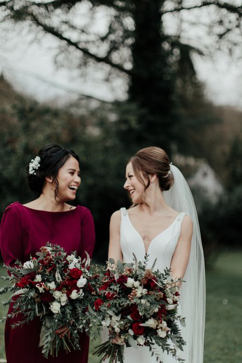 Bride in Essense of Australia Wedding Dress with Straps and Cathedral Length Veil and Bridesmaid in Burgundy Dress