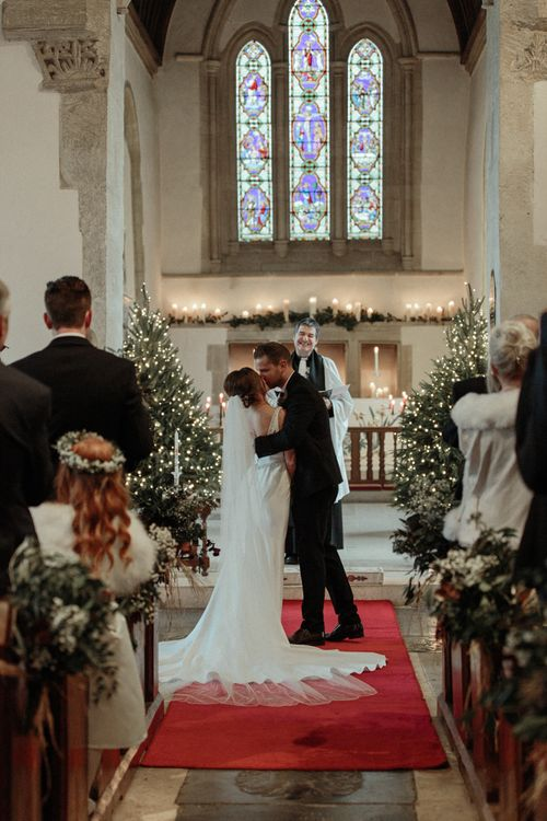 Church Wedding Ceremony with Bride in Essense of Australia Wedding Dress and Groom in Marks and Spencer Suit Kissing at the Altar