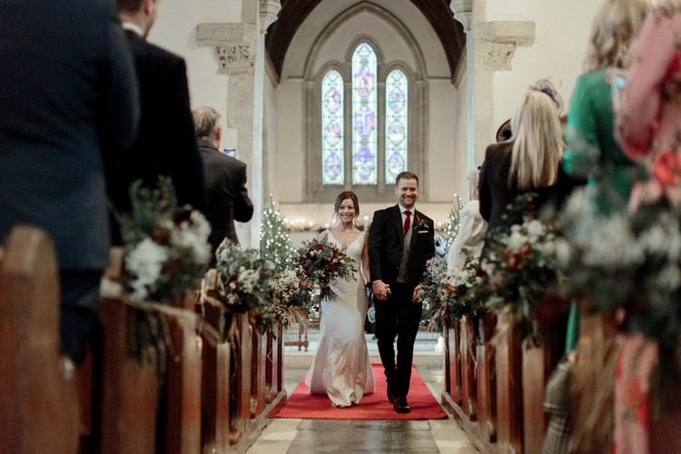 Bride in Essense of Australia Wedding Dress and Groom in Marks and Spencer Suit Walking Up the Church Aisle