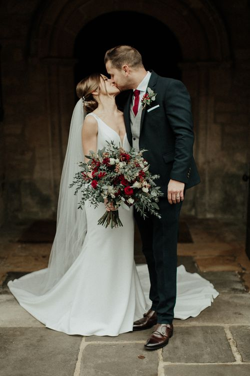 Bride in Essense of Australia Wedding Dress Holding a Red Flower and Foliage Bouquet and Groom in Marks and Spencer Suit Kissing Outside the Church