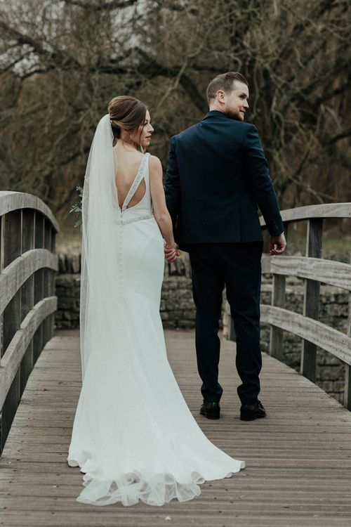 Bride in Essense of Australia Wedding Dress and Cathedral Veil and Groom in Marks and Spencer Suit Holding Hands