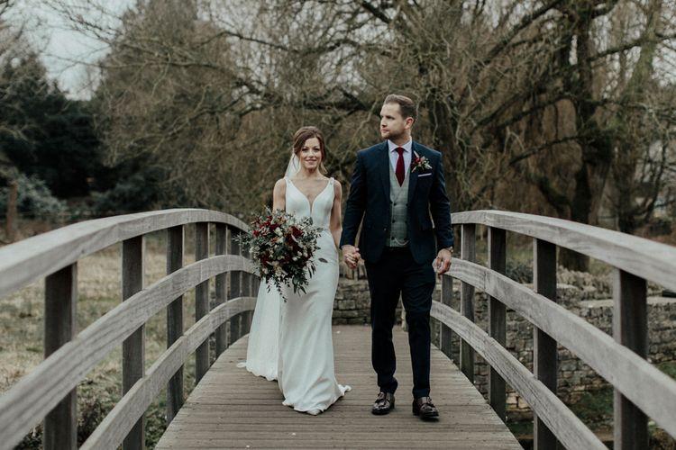 Bride in Essense of Australia Wedding Dress and Cathedral Veil and Groom in Marks and Spencer Suit Walking on a Bridge at Cripps Barn