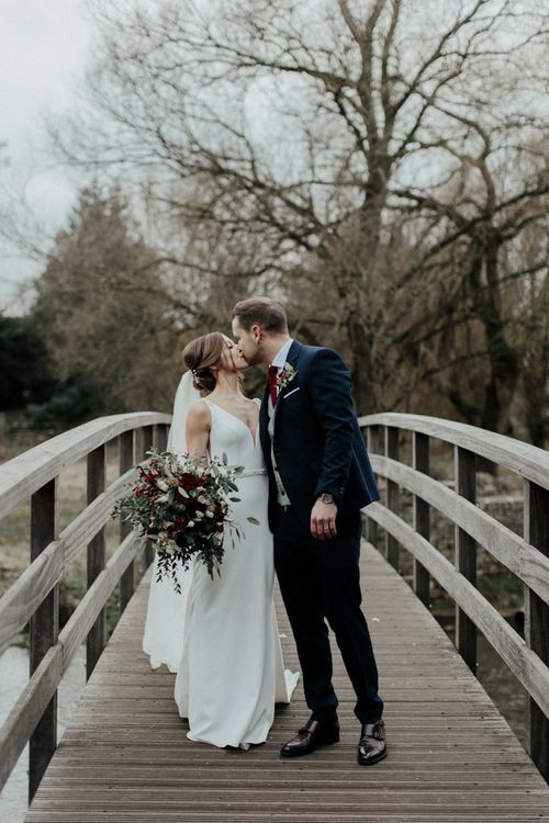 Bride in Essense of Australia Wedding Dress and Cathedral Veil and Groom in Marks and Spencer Suit Kissing
