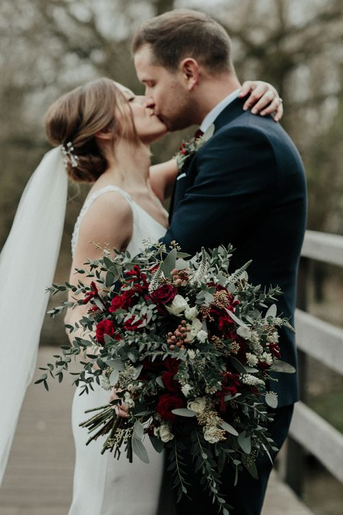 Green and Red Winter Wedding Bouquet with Bride in Essense of Australia Wedding Dress and Cathedral Veil and Groom in Marks and Spencer Suit