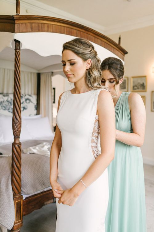 Bridesmaid Helping the Bride into Her Fitted Pronovias Wedding Dress with Lace Side Panels