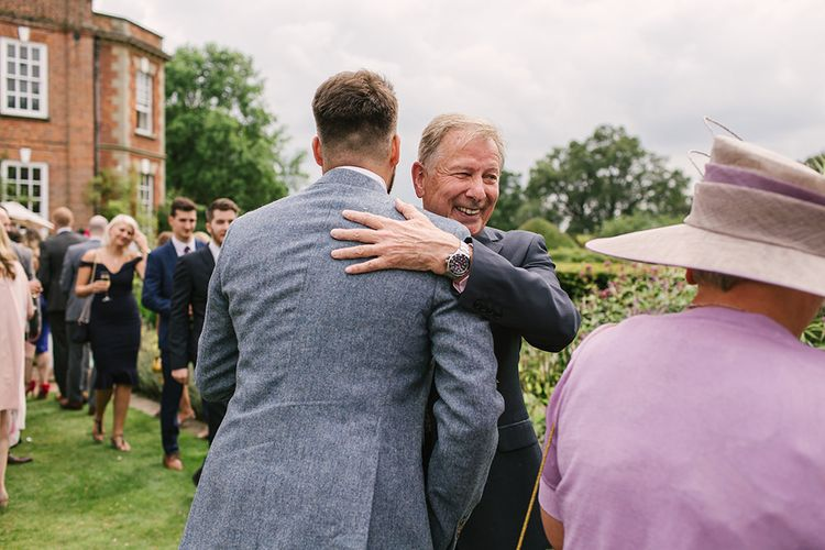 Groom in Grey Wedding Suit Being Congratulated by Wedding Guests