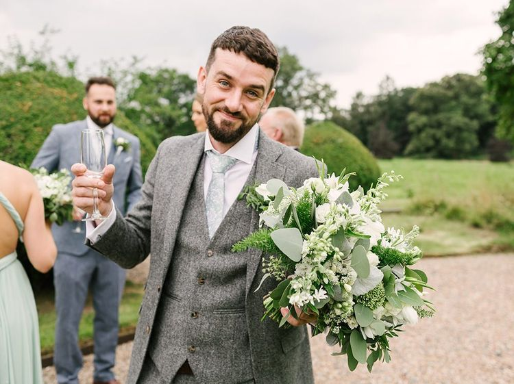 Groomsman in Grey Wedding Suit Holding a White and Green Wedding Bouquet