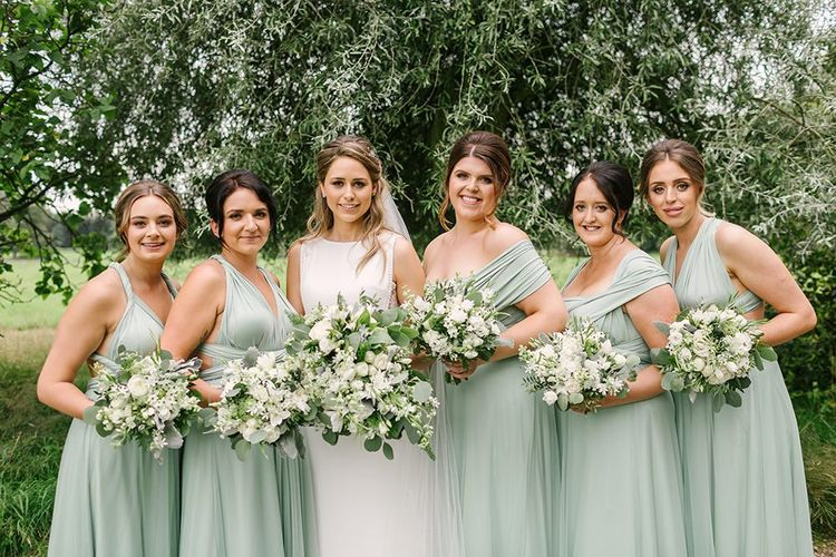 Bridal Party Portrait with Bridesmaids in Pale Green Multiway Dresses and Bride in Pronovias Wedding Dress Holding White Flower and Foliage Bouquets
