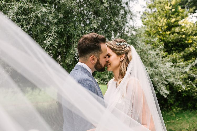 Bride and Groom Kissing with the Brides Veil Blowing in the Wind