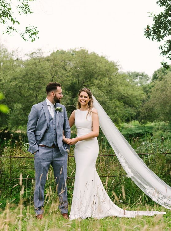 Bride in Fitted Pronovias Wedding Dress Holding Her Grooms Arm  in a Light Grey Wedding Suit