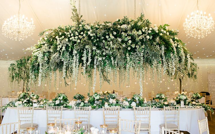 White Flower and Green Foliage Floral Installation Over the Top Table by Red Floral Architecture