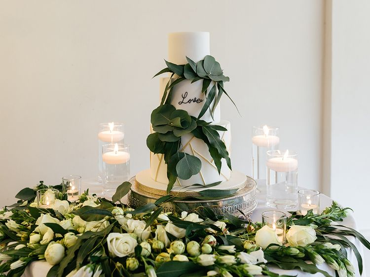 White Wedding Cake Surrounded by Foliage and Candles