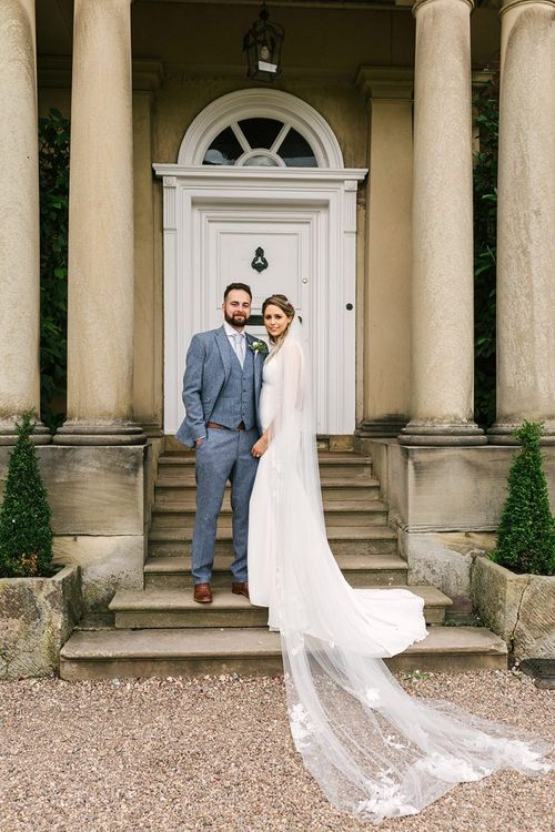 Bride in Pronovias Wedding Dress and Cathedral Length Veil and Groom in Grey Wedding Suit