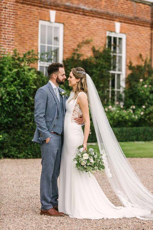 Bride in Pronovias Wedding Dress with Lace Side Inserts and Groom in Light Grey Wedding Suit
