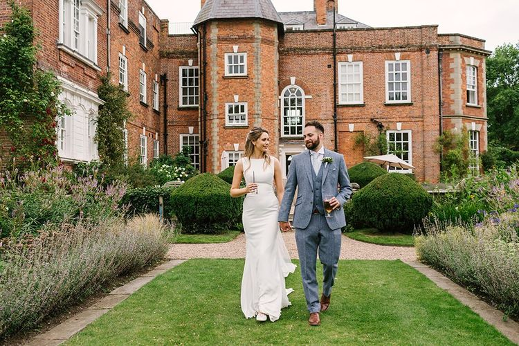 Bride in Pronovias Wedding Dress and Groom in Light Grey Wedding Suit Holding Hands Outside Iscoyd Park Wedding Venue