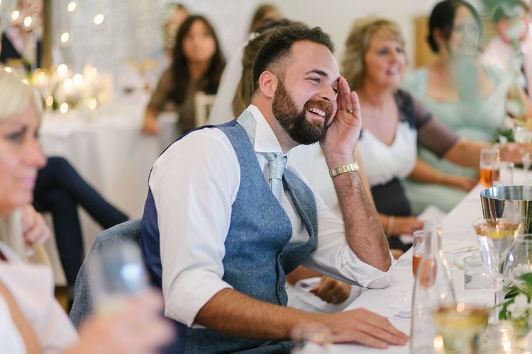 Groom in Grey Wool Waistcoat Laughing During the Wedding Reception Speeches