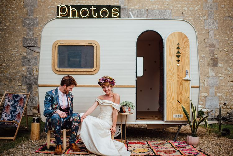 Caravan Photo Booth For Wedding // Secret Garden Party Inspired Wedding France Bride In Large Faux Floral Crown And Glitter Station With Groom In Floral Print Suit & Images From The Shannons