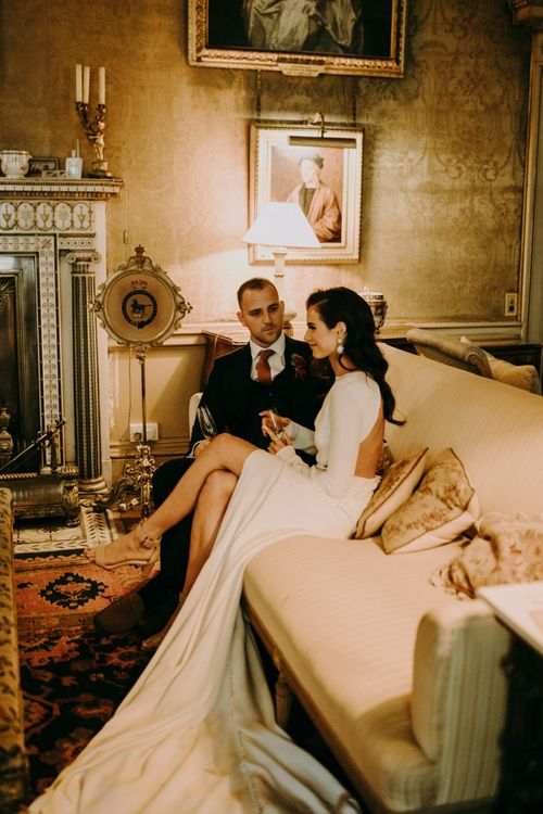 Bride and Groom Relaxing on The Sofa Showing Bride Split  Design in Her Dress