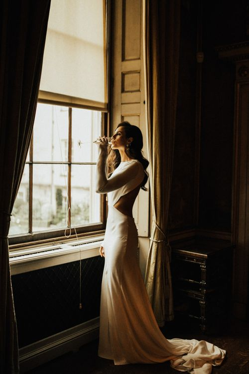 Beautiful Bride Standing at The Window  Sipping Champagne