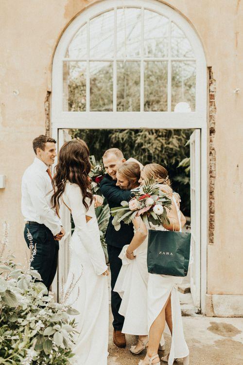 Bride and Groom Embracing Wedding Guests