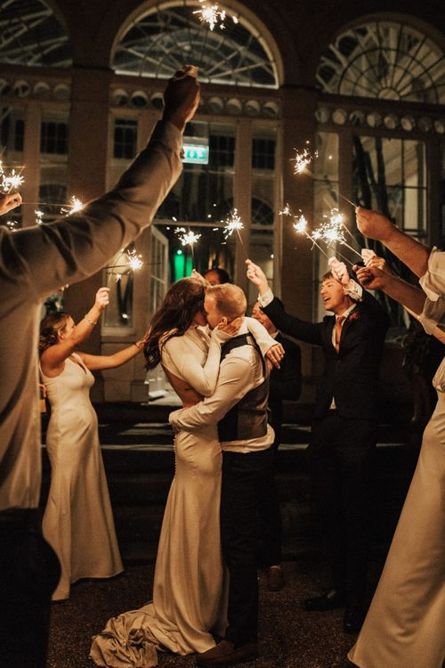 Bride and Groom Kissing During Sparkler Moment