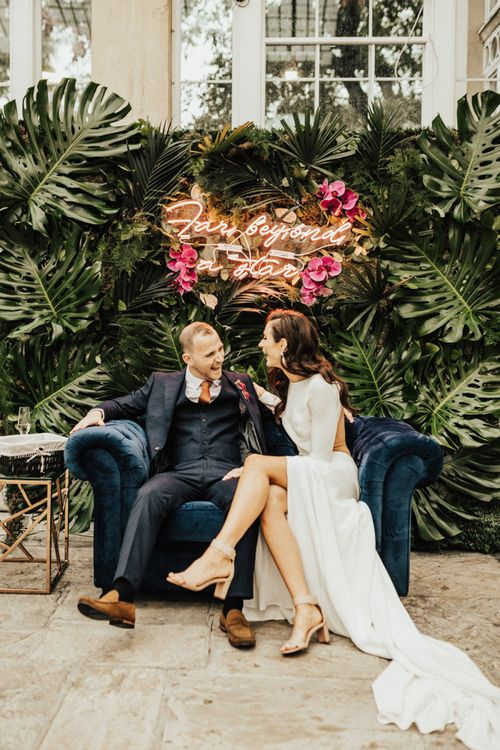 Bride and Groom Sitting on a Love Seat with Neon Sign Wedding Sign