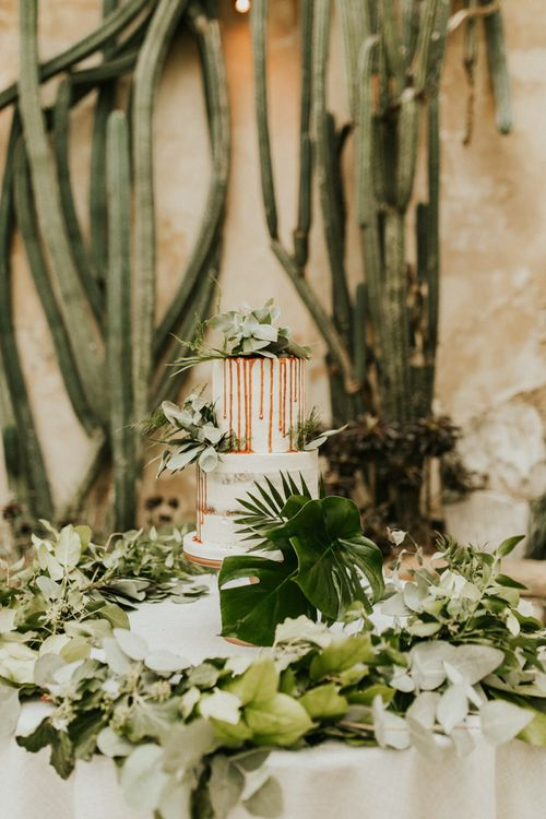 Two Tier Semi Naked Wedding Cake with Drip Decor and Greenery Backdrop