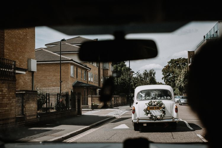 White Wedding Car with Flower Garland and Ribbons | Floral Arch and Bride in Batwing Sleeve Halfpenny Dress for London Pub Wedding | Caitlin + Jones
