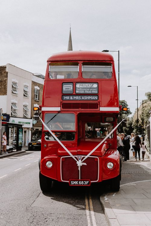 Red London Bus for Wedding Party | Floral Arch and Bride in Batwing Sleeve Halfpenny Dress for London Pub Wedding | Caitlin + Jones