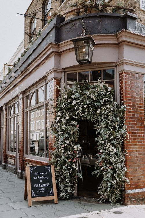Floral Arch | Chalkboard Welcome Sign | Wedding Reception at The Star Pub, Highgate | Floral Arch and Bride in Batwing Sleeve Halfpenny Dress for London Pub Wedding | Caitlin + Jones