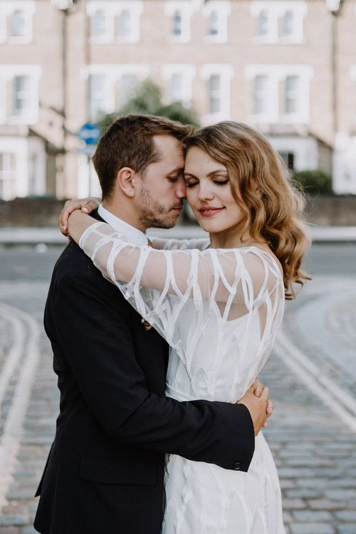 Bride in Embroidered Tulle Halfpenny London Dress with High Neckline, Batwing Sleeves and Low V-Back | Groom in Navy Slim Fit Suit with Checked Double Breasted Waistcoat and Blush Pink Knitted Tie | Floral Arch and Bride in Batwing Sleeve Halfpenny Dress for London Pub Wedding | Caitlin + Jones
