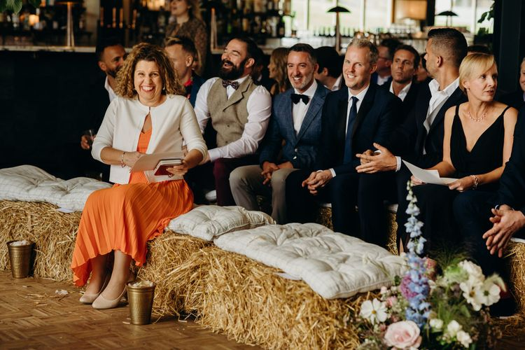 Guests Sitting on Hay Bales at Ceremony