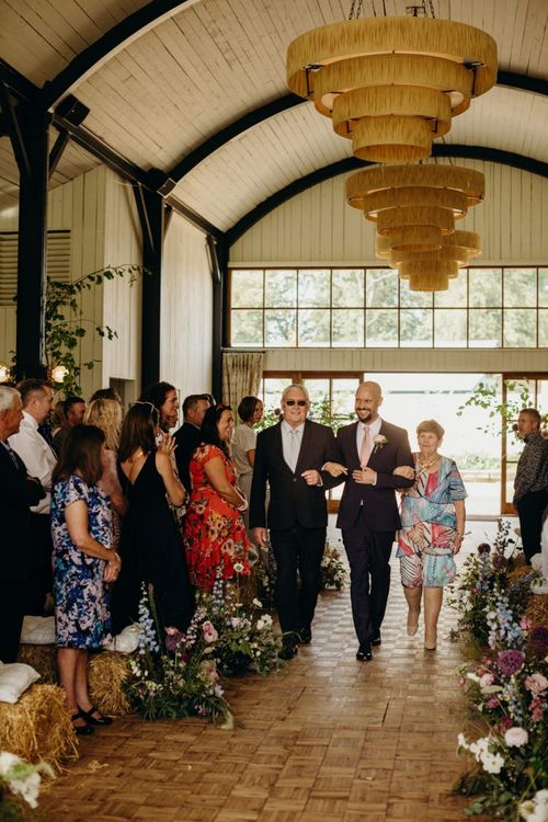 Groom Walking Down the Aisle with His Parents during the Ceremony