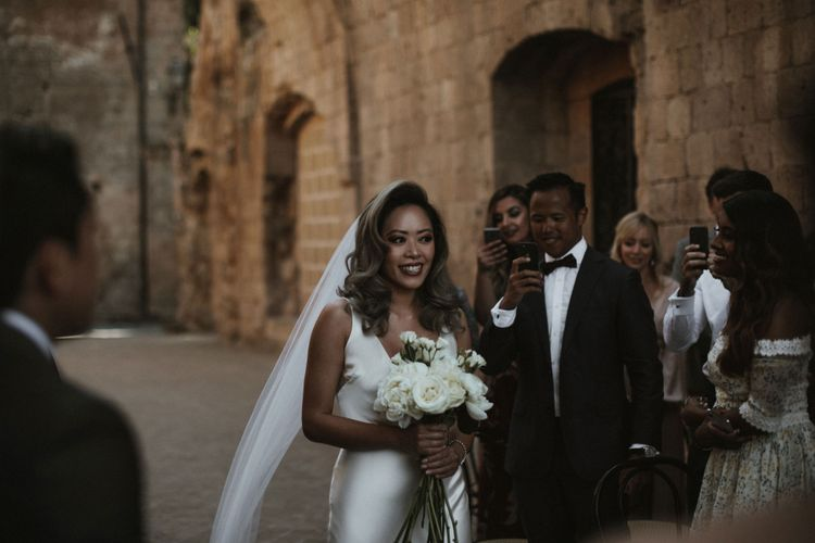 Entrance of the Bride   Bride in Silk Pallas Couture Wedding Dress with Plunging Neckline and Side Split   Roman & French Cathedral Veil   Long Stemmed Bridal Bouquet of White Flowers   Intimate Italian Castle Wedding with Prosecco Tower   James Frost Photography