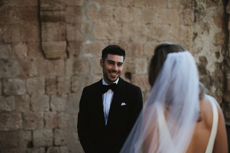 Wedding Ceremony   Groom in Made to Measure Tuxedo Suit by Oscar Hunt   Black Aquila Shoes   Bride in Silk Pallas Couture Wedding Dress with Plunging Neckline and Side Split   Roman & French Cathedral Veil  Intimate Italian Castle Wedding with Prosecco Tower   James Frost Photography