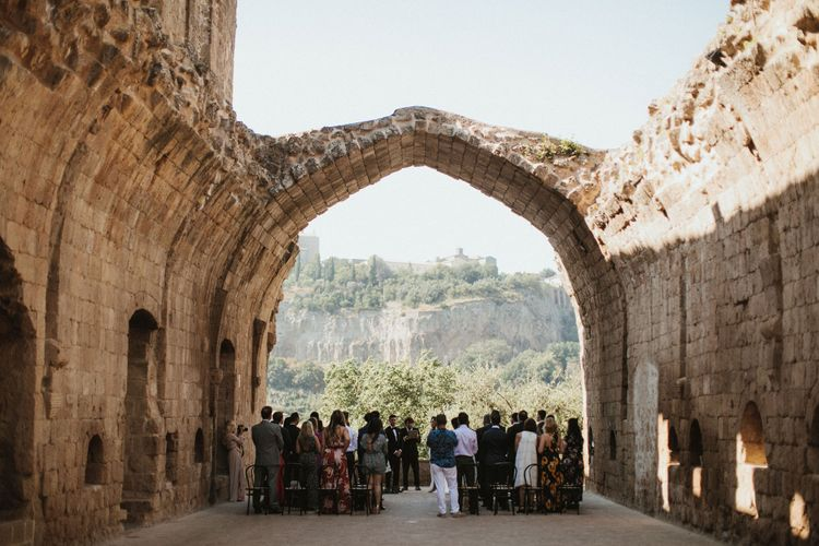 Wedding Ceremony Under the Arch at La Badia Di Orvieto Italy   Intimate Italian Castle Wedding with Prosecco Tower   James Frost Photography